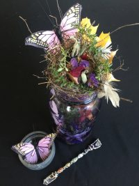 jar of flowers with pink butterfly and a small crystal wand
